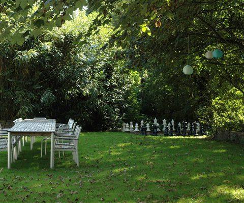 Groepshuis in Drenthe met ruime besloten en tuin en een schaakbord buiten.