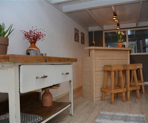 Groepshuis Hiekerhoes huiskamer met barretje en houtkachel.