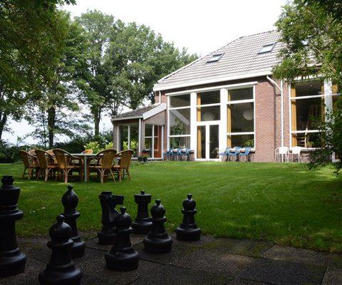 Groepsaccommodatie in Drenthe met ruime tuin met schaakbord.
